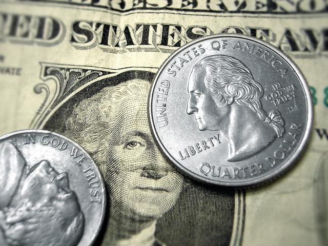 kovové mince položená na papírových bankovkách